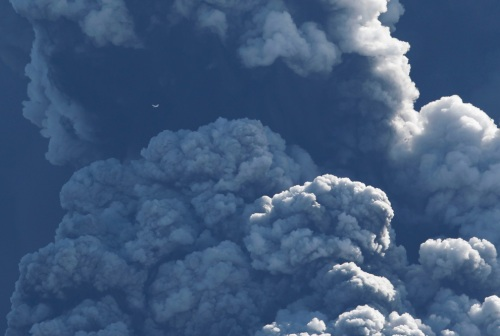 A small plane (upper left) flies past smoke and ash billowing from a volcano in Eyjafjallajokul, Iceland on April 17, 2010. (REUTERS/Lucas Jackson) #